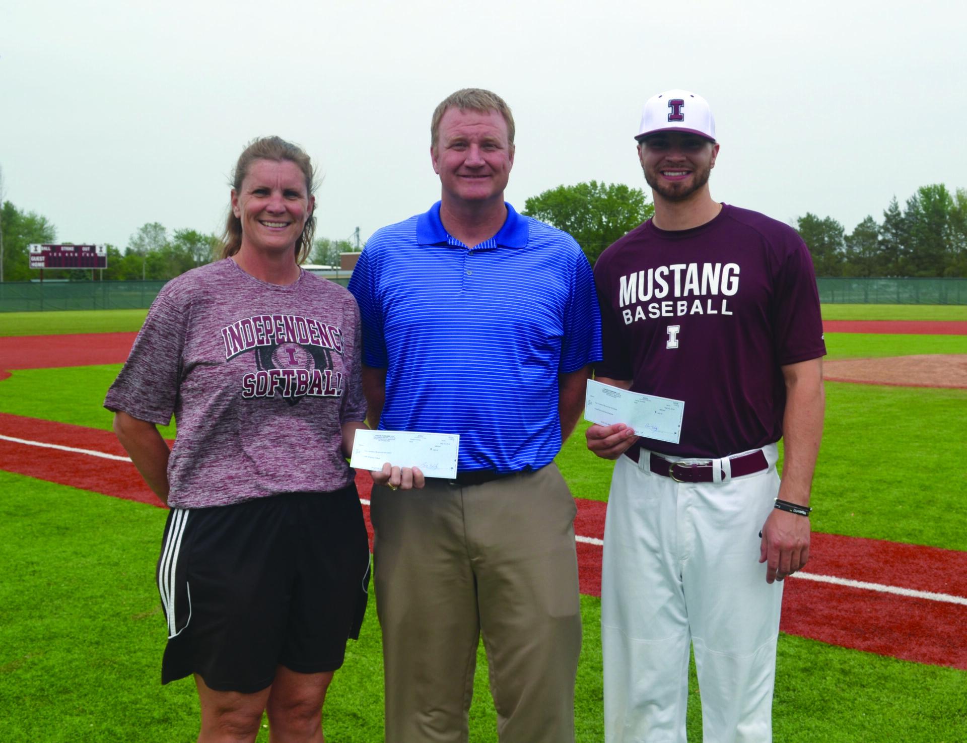 Head Softball Coach- Heather Hupke and Head Baseball Coach- Jimmy Lizarraga are presented checks by Fusion Forward, LLC president Mike Hamilton