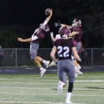 Independence football player reaches up to catch a pass