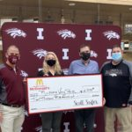 Assistant principal Dewey Hupke and head baseball coach Matt Miller accept a check for $2500.00 from Lisa and Scott Soifer of Soifer McDonald's. The Soifer's are supporting a project to improve batting cages, storage and seating opportunities at Mustang Way Park.